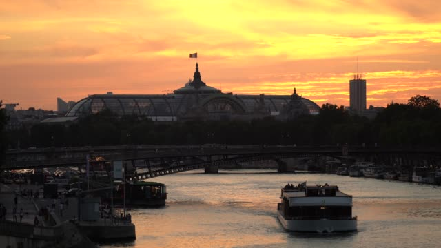 general view during sunset of the grand palais, next to the seine river where boats can be seen, on july 15, 2020 in paris, france. - はしけ点の映像素材/bロール