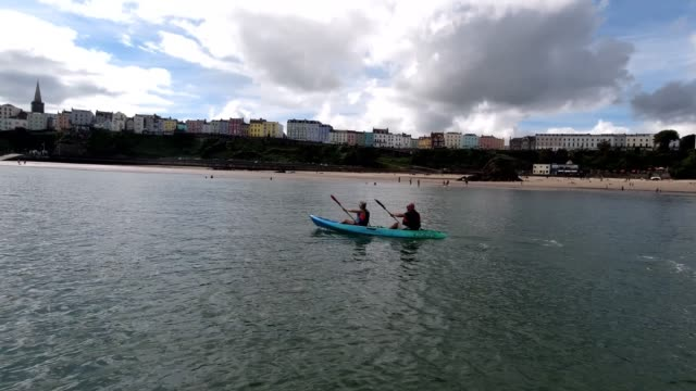 general view of a couple paddle their kayak along north beach, on sept 6, 2020 in tenby, wales, united kingdom. tourism is still recovering in wales... - oar stock videos & royalty-free footage