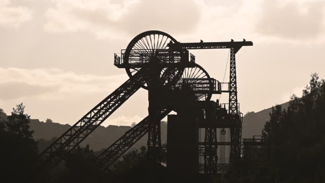 a general view of a silhouetted mine shaft tower at the rhondda heritage park in the former mining community of trehafod at sunrise in the rhondda... - mine shaft stock videos and b-roll footage