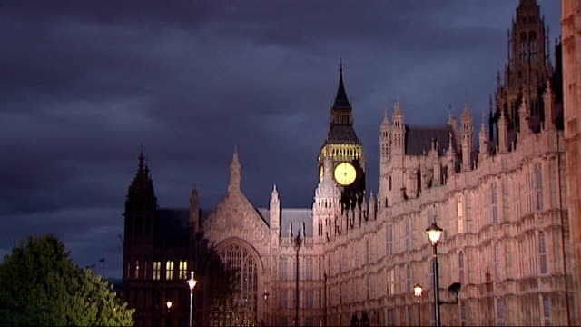 vídeos y material grabado en eventos de stock de general view of houses of parliament television lights and cameras on college green - unidentified presenter and interviewee on 'stage' big ben with... - vista general