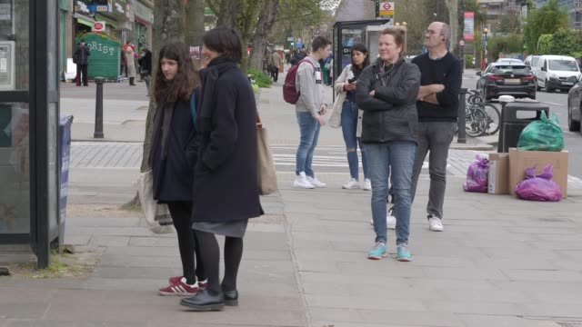 general view of shoppers practising 'social distancing' by keeping two meters apart from each other as they queue outside a shop as british prime... - social distancing stock videos & royalty-free footage
