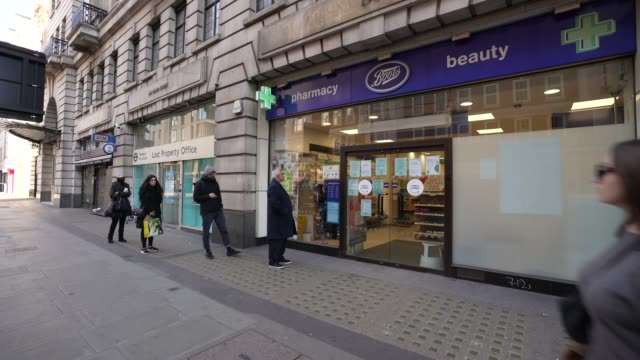 general view of shoppers queuing outside boots pharmacy as they practise social distancing as the uk government tells the public to stay at home and... - buying stock videos & royalty-free footage