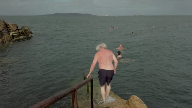 a general view of the forty foot a historic bathing pool near dun laoghaire in dublin bay once a male only swimming spot the forty foot was made... - james joyce stock-videos und b-roll-filmmaterial