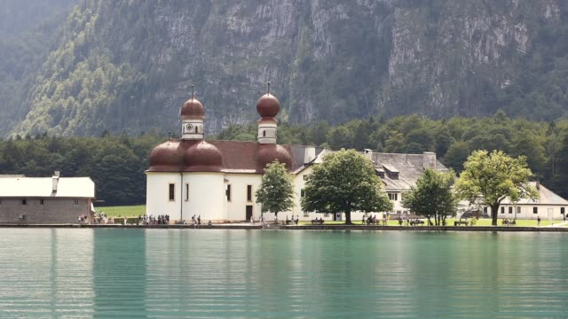 general view of the roman catholic st. bartholomew's church is seen from koenigssee lake side on july 30, 2019 in koenigssee, germany. - catholicism stock videos & royalty-free footage