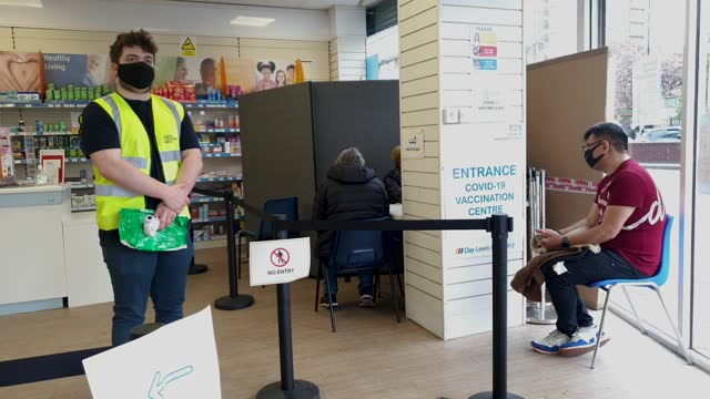 general view of volunteer daniel murray and members of the public as they wait in a queue to receive their dose of the covid vaccine at the nhs... - brian dayle coronavirus stock videos & royalty-free footage
