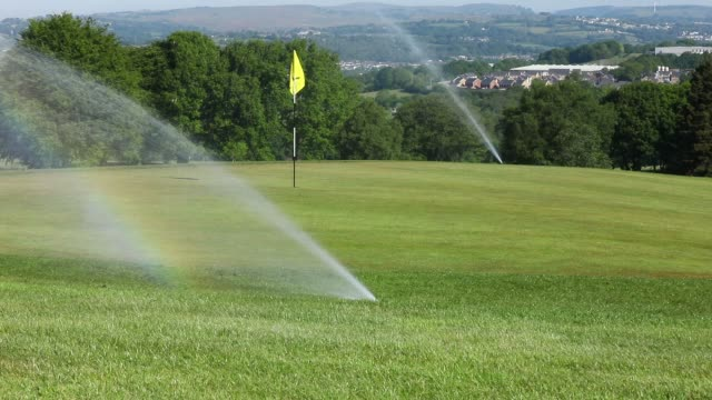 a general view of water sprinklers watering a green at bryn meadows golf club tees off at as restrictions on playing golf in wales have been eased... - green golf course stock videos & royalty-free footage
