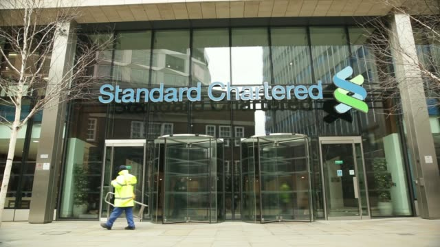 vídeos de stock e filmes b-roll de general view signage above the entrance to the headquarters of standard chartered plc in london, u.k., on friday, march 7 workmen walk past standard... - vista geral