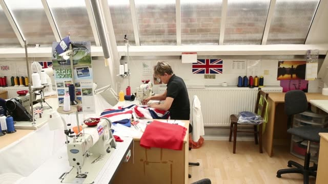 stockvideo's en b-roll-footage met general views a worker pins material together ahead of sewing a section of british union flag during manufacture at the flagmakers workshop, a unit... - alle vlaggen van europa