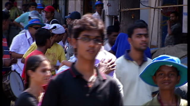 general views and cricket practice in mumbai drummers along and playing on street sot / bollywood film star on poster / woman selling chillies at... - bollywood stock videos and b-roll footage