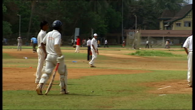 General views and cricket practice in Mumbai More matchplay / Other players applauding from sidelines / Poster for Macho Cricket Club / Other players...