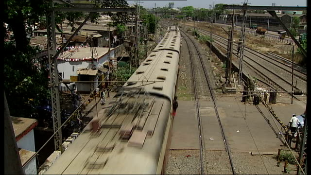 General views and cricket practice in Mumbai Passengers along at railway station as train horn sounds and train along from station SOT/ People along...