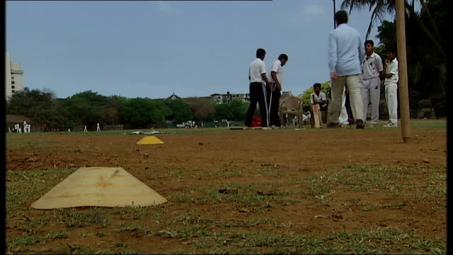 General views and cricket practice in Mumbai Pitch being rolled as practice takes place in background / Players practicing batting in nets /...