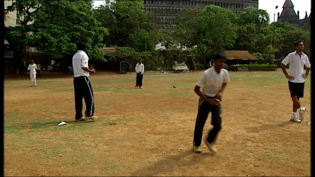 General views and cricket practice in Mumbai Vendor pushing cart across field as cricketers continue to play / Players practicing in the nets...