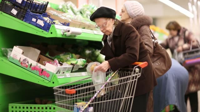 general views customers enter and exit a dixy supermarket operated by oao dixy group in moscow russia on tuesday april 8 different brands of olive... - 凍った点の映像素材/bロール