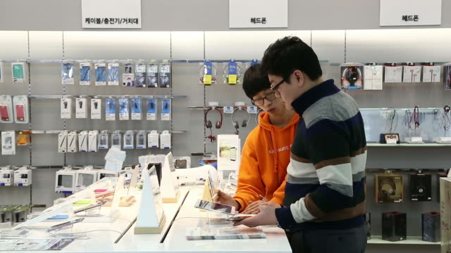 General views customers look at Samsung Electronics Co products at the company's mobile store in Seoul South Korea on Friday Jan 3 An employee helps...