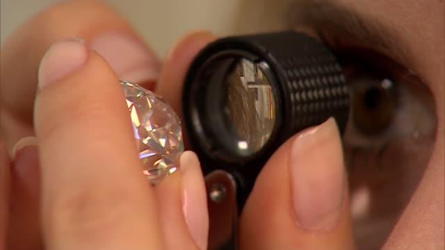 General views diamond ring at Sotheby's ENGLAND London Sotheby's INT Various shots woman inspecting diamond ring / GVs diamond