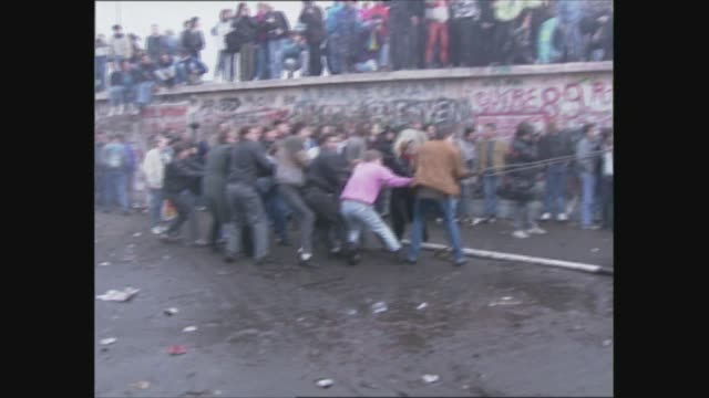 general views east berlin and opening of berlin wall east germany east berlin ms crowd trying to pull down section of wall with chain water cannon... - 1989 bildbanksvideor och videomaterial från bakom kulisserna