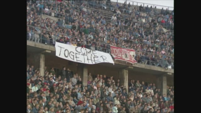 general views east berlin and opening of berlin wall; west germany: west berlin: olympic stadium: ext/dusk gv's crowd at football match; banner... - 西ドイツ点の映像素材/bロール