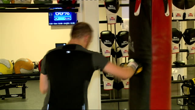 stockvideo's en b-roll-footage met general views inside virgin active gym; england: london: int man using weight machine in virgin active gym / man punching punch bag / people working... - vrijetijdsfaciliteiten