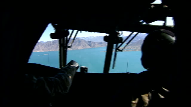 General views Kajaki Dam and British soldiers manning positions INT HELICOPTER View from inside cockpit of Chinook helicopter as flies over Kajaki...