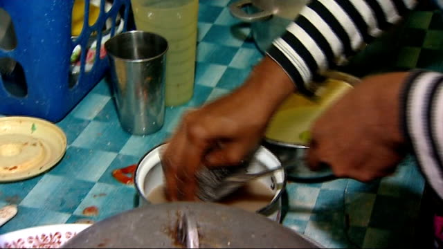 vídeos de stock e filmes b-roll de general views markets, street scenes, food aid distribution, shanty town; int woman placing groceries on table / woman washing cooking utensils in... - hispaniola