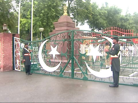 general views more of 'pakistani soldiers 'beating the retreat' ceremony with pakistan flag flying over building tower / soldiers marching and... - 式典点の映像素材/bロール