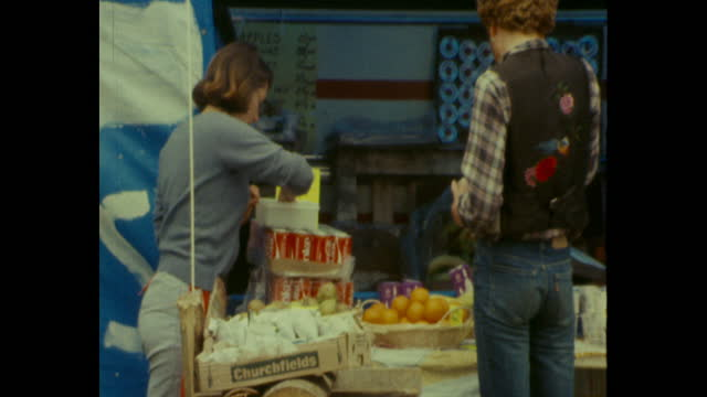 general views of 1983 glastonbury festival showing flush toilets, people buying food and women using spinning wheel - spinning stock videos & royalty-free footage