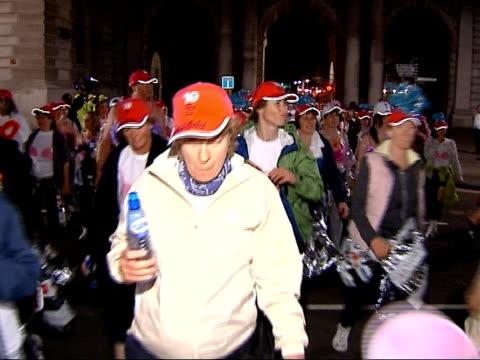 stockvideo's en b-roll-footage met general views of 2007 moonwalk charity fundraiser moonwalk competitors crossing road including male walkers wearing bras women wearing 'mouse ear'... - haaraccessoires