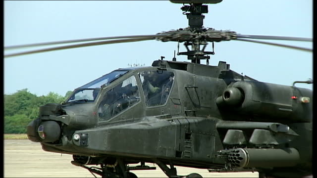 general views of apache helicopters at raf wattisham / soldiers marching ground crew carrying out checks / close shot of pilots in helicopter cockpit... - apache helicopter stock videos and b-roll footage