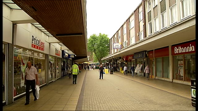 General views of Basildon Shoppers along past grey concrete pillars / Low angle view of brick and glass building / Shops in shopping arcade with...
