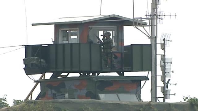 general views of border area armed south korean soldier watching thru binoculars in observation tower on south side of border / soldiers in... - south korea stock videos and b-roll footage