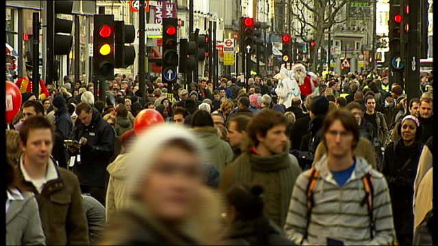 """stockvideo's en b-roll-footage met general views of christmas shoppers in oxford street; ext shoppers along past store displaying sign reading """"20% off everything in store today' int... - bord weg afgesloten"""