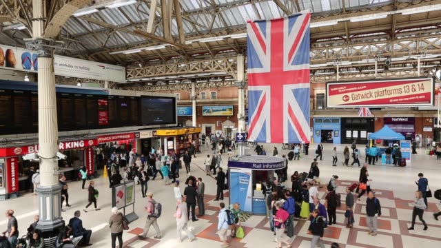 general views of commuters and tourists at victoria station in london uk large union jack flags decorate the station - railway station platform stock videos & royalty-free footage
