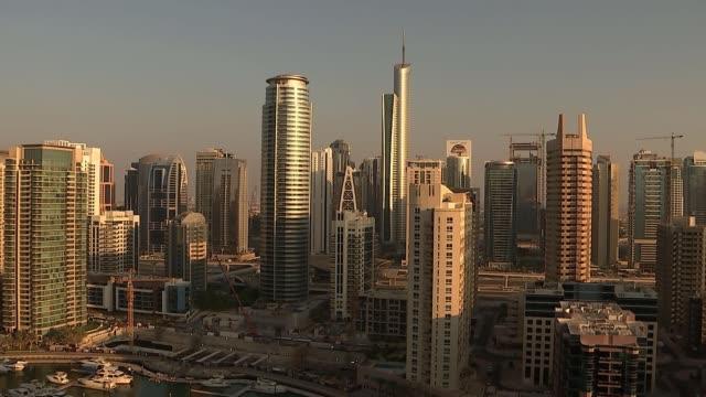 general views of dubai united arab emirates dubai ext wide shot of city sightseeing bus on bridge as yacht along water / yachts in marina / city... - crane stock videos & royalty-free footage