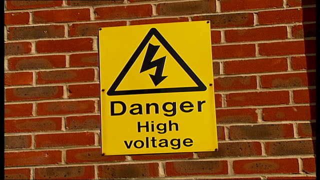 General views of electricity substation EXT Yellow warning sign reading 'Danger High Voltage' displayed on brick wall