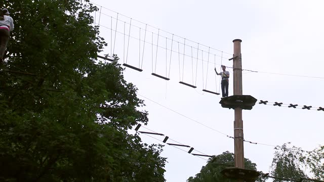 general views of go ape adventure park; england: london: ext various of people along high ropes course at go ape adventure park / go ape workers - adventure stock videos & royalty-free footage