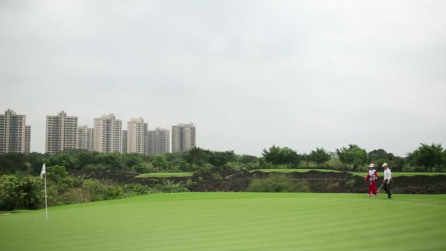 general views of golfers on the golf course at mission hills resort haikou on hainan province china on saturday april 5 mission hills logo on the... - ゴルフクラブ点の映像素材/bロール