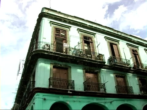 vídeos de stock, filmes e b-roll de general views of havana and the daily lives of cubans el capitolio / people walking along street past mint green building with shuttered balconies /... - parque green