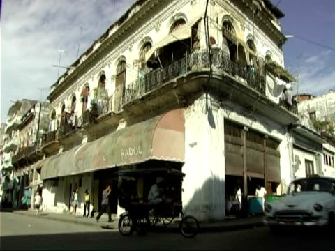 general views of havana and the daily lives of cubans traffic and pedestrians along road / men sitting on back of truck man mending electrical... - イスパニョーラ点の映像素材/bロール