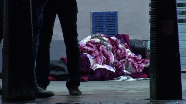 vídeos y material grabado en eventos de stock de general views of homeless at night; person sleeping under bundle of blankets at charing cross station / station sign / nighttime street views /... - manta ropa de cama