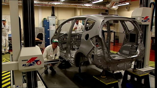 general views of honda plant in swindon car chassis being worked on by robots and worker checking / engineers working on chassis - ホンダ点の映像素材/bロール