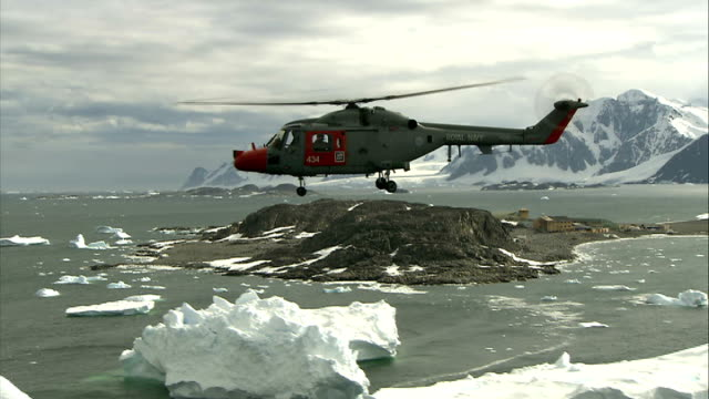 scientists' camp / crevasse abseiling / hms endurance heli views of royal navy helicopter flying over grey antarctic sea and icebergs **slightly... - crevasse stock videos & royalty-free footage