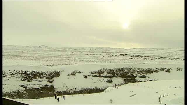 general views of icelandic scenery gv waterfalls in snowy landscape / people along in snow covered landscape as sun low in sky swans and ducks in... - landscape scenery点の映像素材/bロール