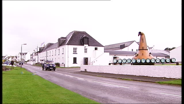coastline and bruichladdich distillery bruichladdich distillery int general views and close shots of barrels of scotch whisky / exteriors of... - scotch whiskey stock videos and b-roll footage