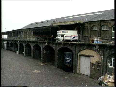 stockvideo's en b-roll-footage met general views of kings cross in the late 1980s various of rundown area around railway arches / cars parked beneath railway arches / dog playing in... - station london king's cross