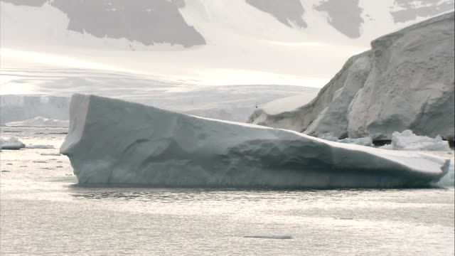 ice floes / crevasse / mountains good steady long shot of snowcovered mountains seen from sea as sun breaking through clouds / similar shot of big... - crevasse stock videos & royalty-free footage