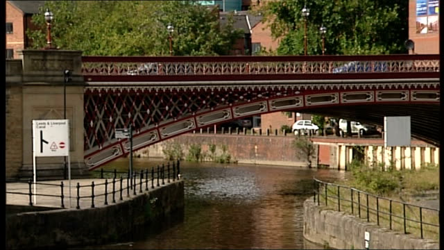 west yorkshire leeds ext several flags flying / various of moored canal boats / various of blocks of flats / bridge over canal / apartments next to... - 全体撮影点の映像素材/bロール