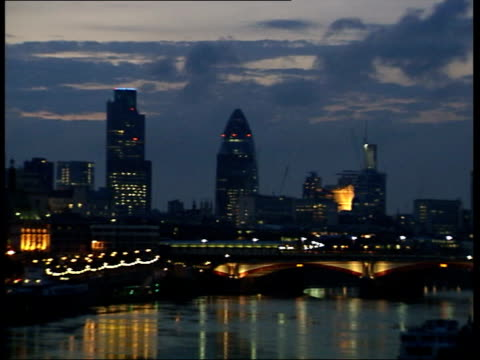 dawn skyline / hyde park / thames long shot of skyscrapers illuminated against dramatic dawn sky seen from thames / good shots of oxo tower gherkin... - swiss re stock videos & royalty-free footage