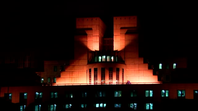 General views of MI6 building at night ENGLAND London Vauxhall Cross General views of illuminated SIS Building / lights reflecting on river Thames /...