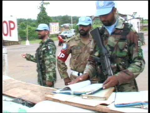 un security checkpoint republic of liberia monrovia ext united nations peacekeeping troops at checkpoint as vehicles drive past / various of un... - 平和維持点の映像素材/bロール